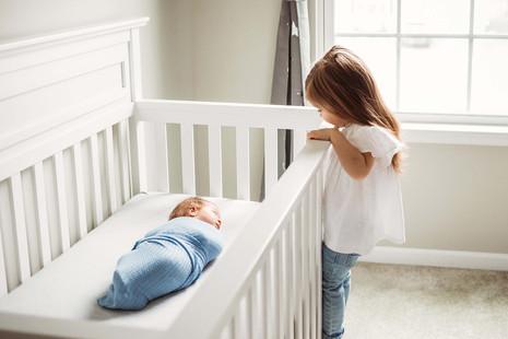 Big sister peeking over baby's crib - Amherst, NY.