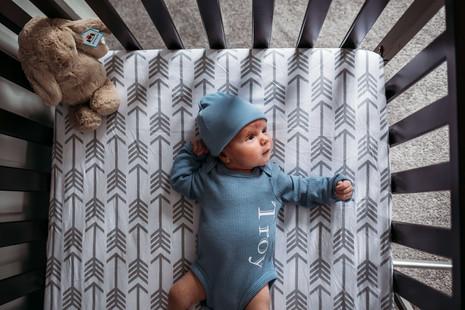 Baby in crib during newborn photos in Buffalo.