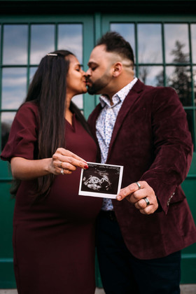 Expectant parents holding ultrasound duing maternity photos.