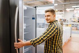 man-choosing-refrigerator-in-electronics