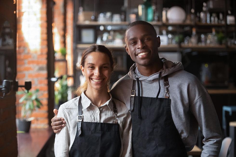 Happy diverse waiter and waitress lookin