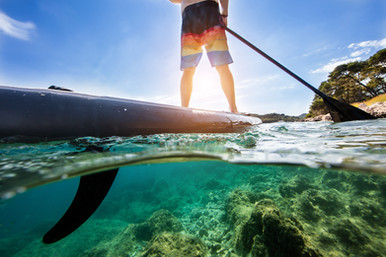 Paddleboarding under and above water composition