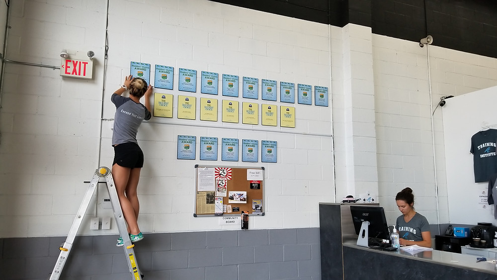 Picture of our Assistant General Manager, Veronika Lloyd, hanging our most recent Reader's Choice awards from the Hamilton News. Hopefully we can add a few more to the wall!