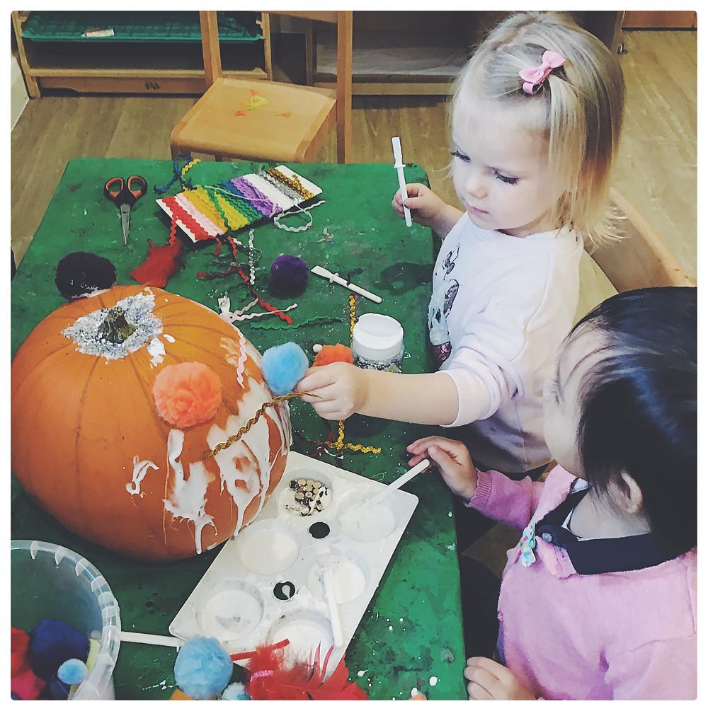 Children decorating a pumpkin