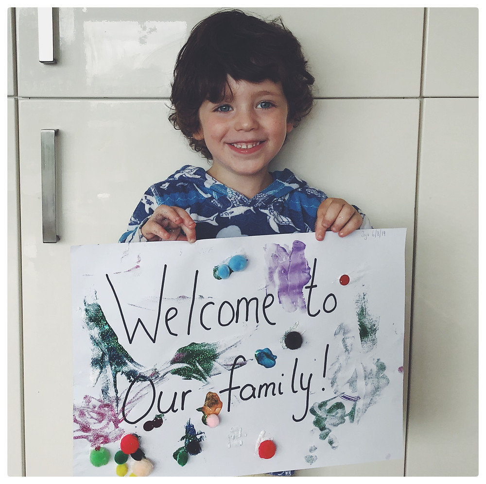 Boy holding a sign displaying, welcome to our family