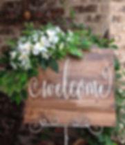 Rètol en fusta i flors de benvinguda al casament