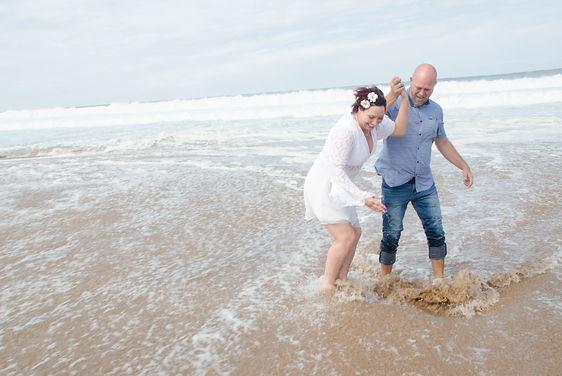 bride and groom laughing in ocean