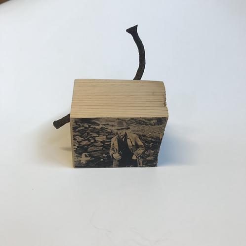Trehus med motiv av Johan Falkberget røker pipe