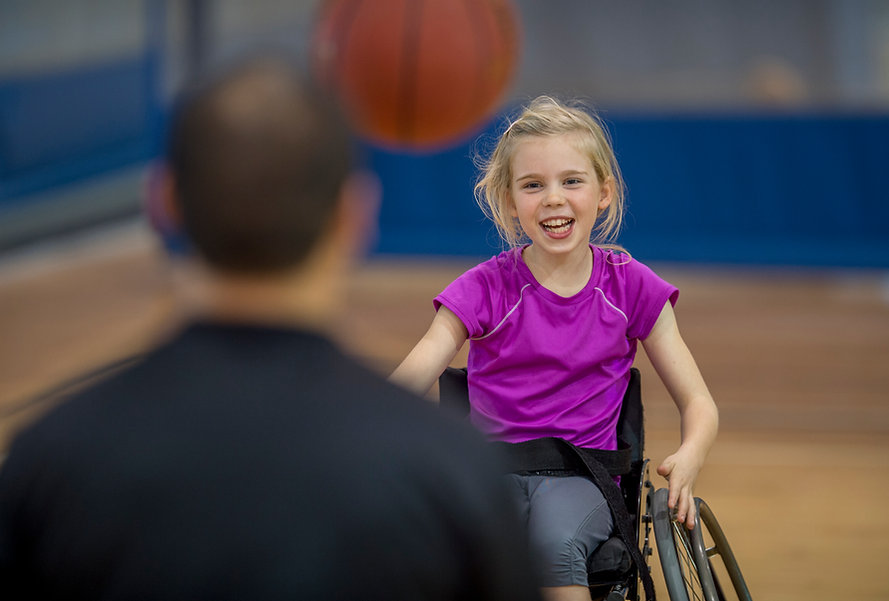A girl plays basketball with a CIL Volunteer