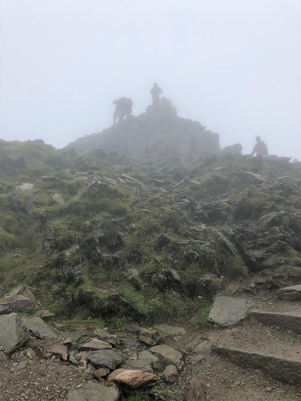 Snowdon summit covered n clouds.  Few people on Snowdon summit