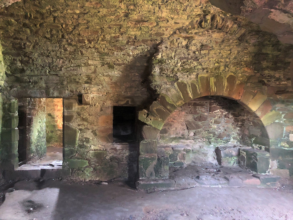 The cellar of the Dunottar Castle Keep housed a kitchen; the stone fireplace remains intact.