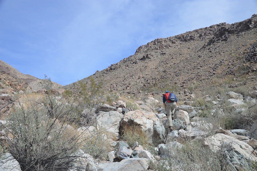 Scrambling over boulders on hike to summit of Pinto Mountain in Joshua Tree National Park