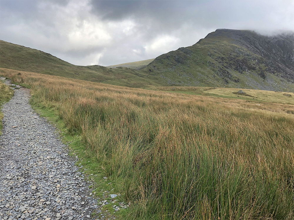 Hiking the Ranger Path along the lower slope of Moel Cynghorion heading to the summit of Snowdon