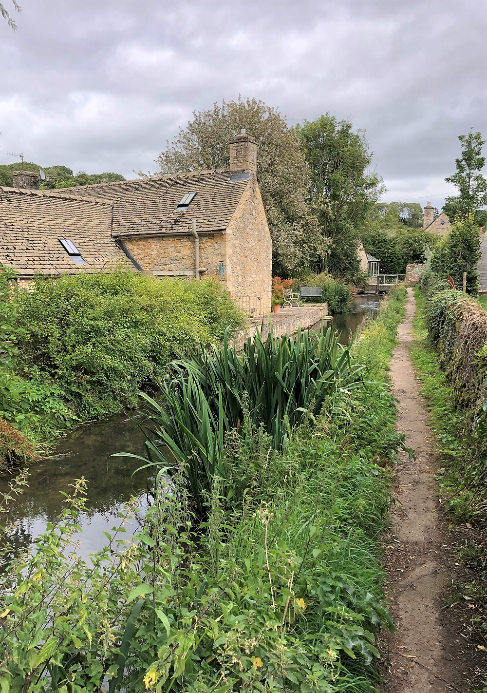 River Windrush flowing through Village of Naunton of the Cotswolds