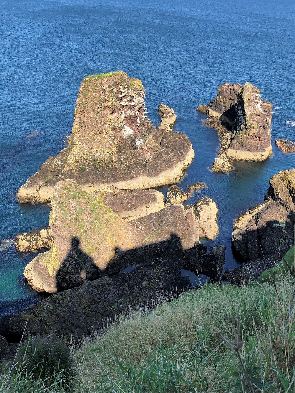 Rock outcroppings rising from the North Sea around Dunnottar Castle