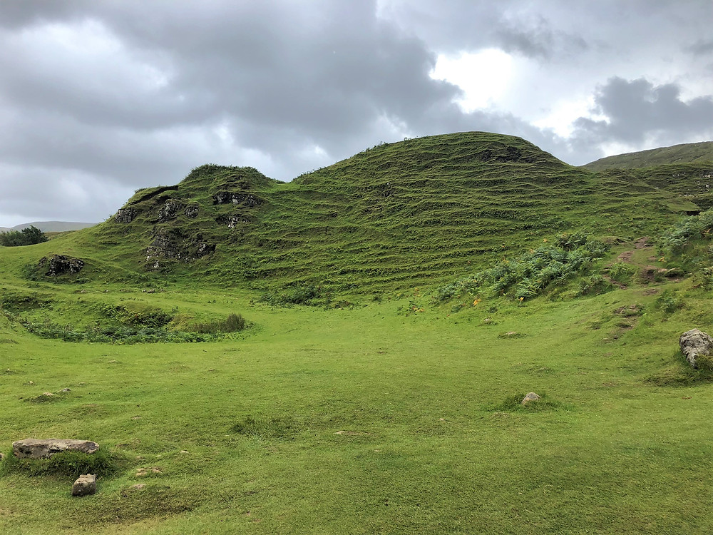 Lush green knolls with grooves in the surface in the Fairy Glen on the Isle of Skye