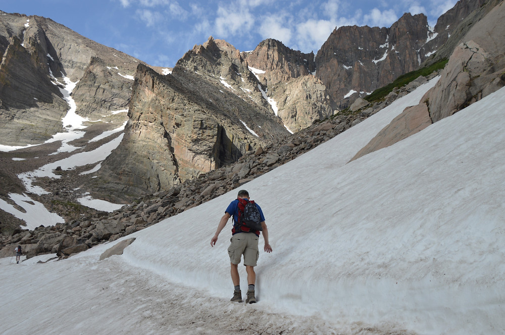 Walking slowly as we cross a snowfield on hike to Chasm Lake in Rocky Mountain National Park