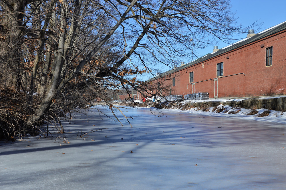 Nashua Manufacturing Co. canal in Mine Falls Park running along old brick mill building