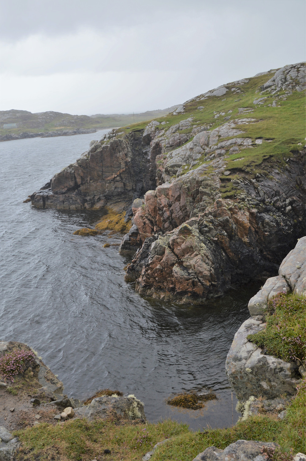 Rocky ledges and sea cliffs rose 50 feet above the water of Loch Roag on Great Bernera Loop hike on the