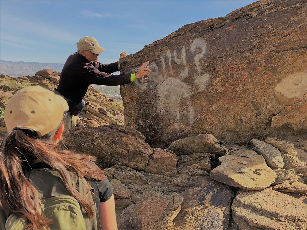 Efforts by Friends of the Desert Mountains organization to remove graffiti from local hiking trails.  Before treatment photo