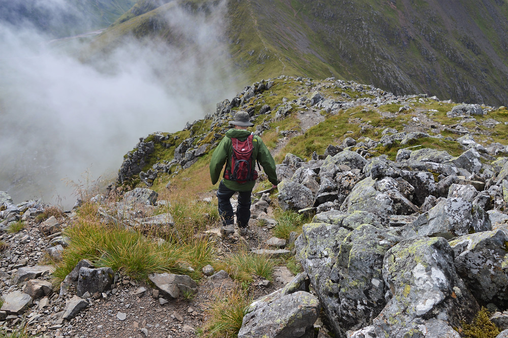 Hiking from the summit of Stob Na Doire down a steep narrow rocky slope
