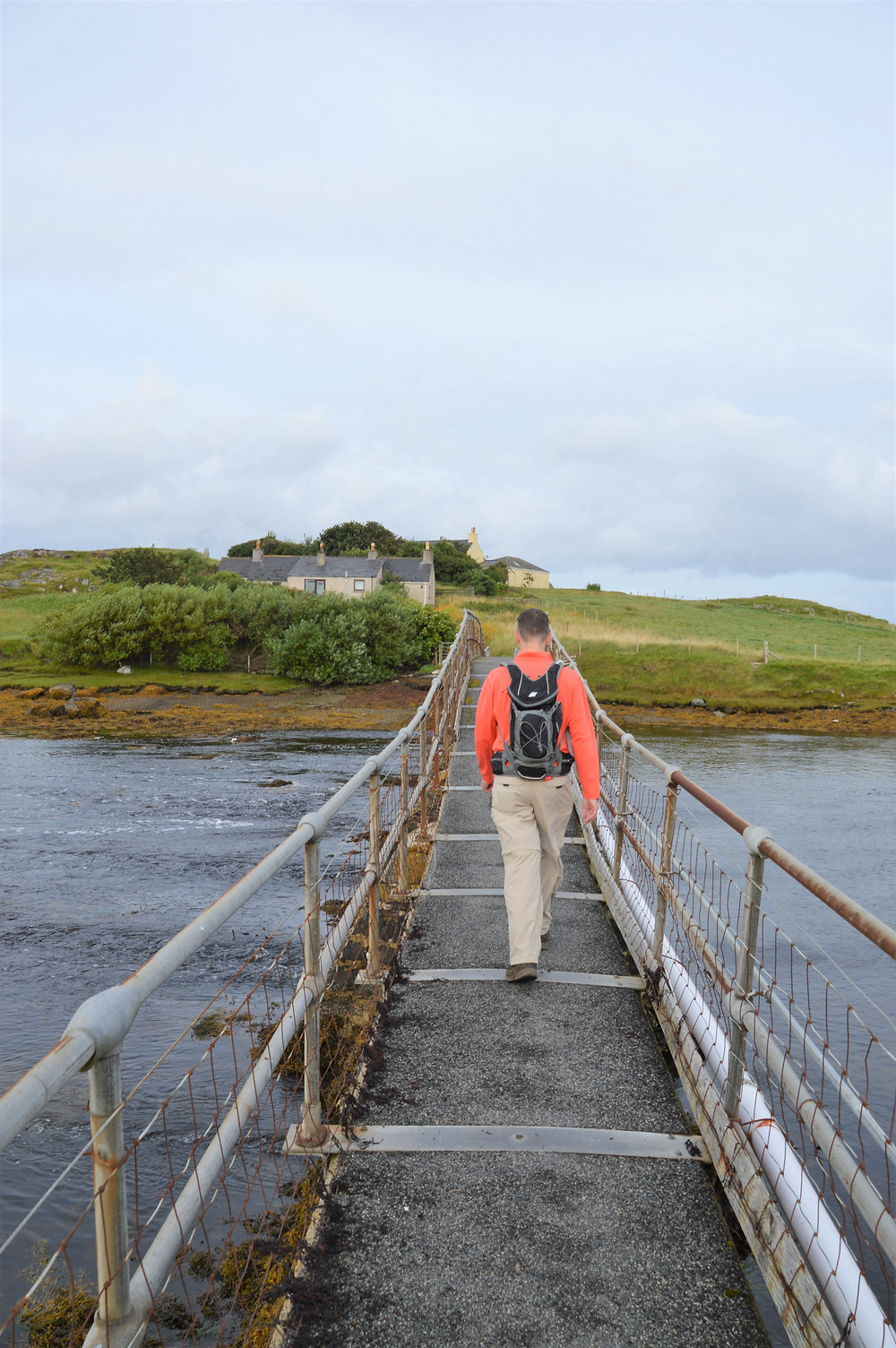 Crossing the foot bridge that spans Tob Bhalasaigh on Great Bernera Loop hike on the NW coast of Isle of Lewis, Outer Hebrides