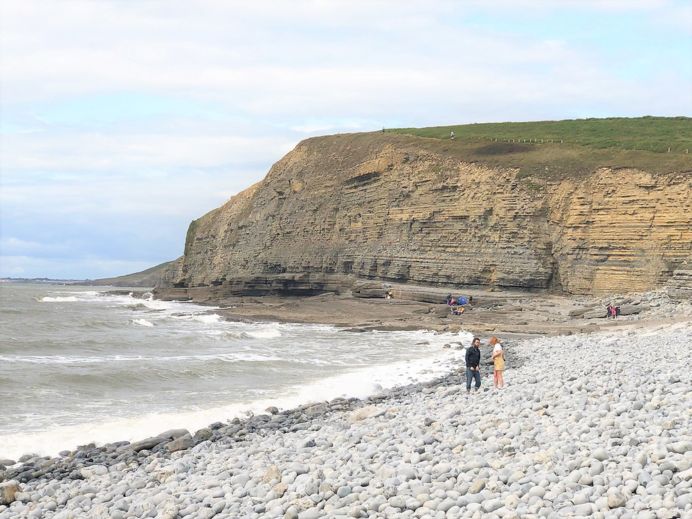 Plunging cliffs and stone covered Dunraven Beach along the Glamorgan Heritage Coastal Trail in Wales