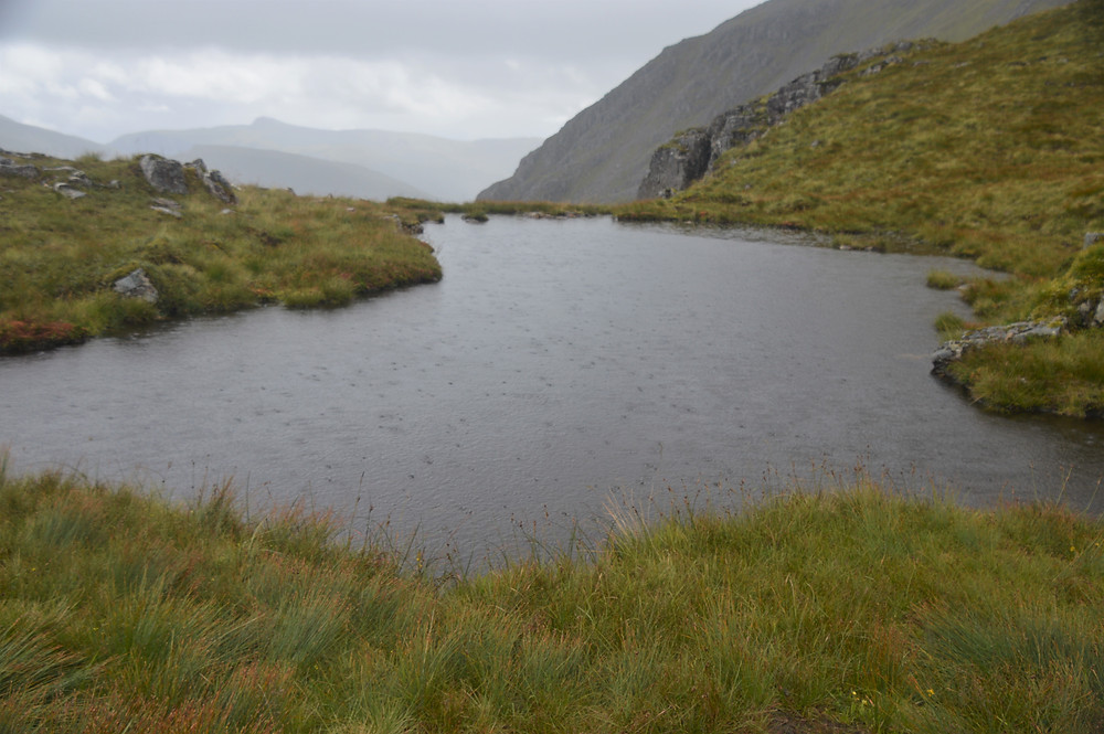 Rain drops on the lochan on the path to Stob Na Doire in the Scottish Highlands