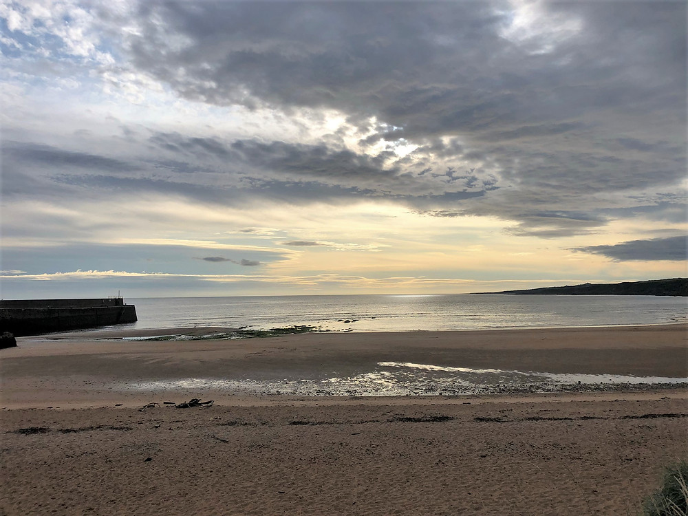 Sunrise on the beach beside St Andrews Cathedral in St Andrews Scotland