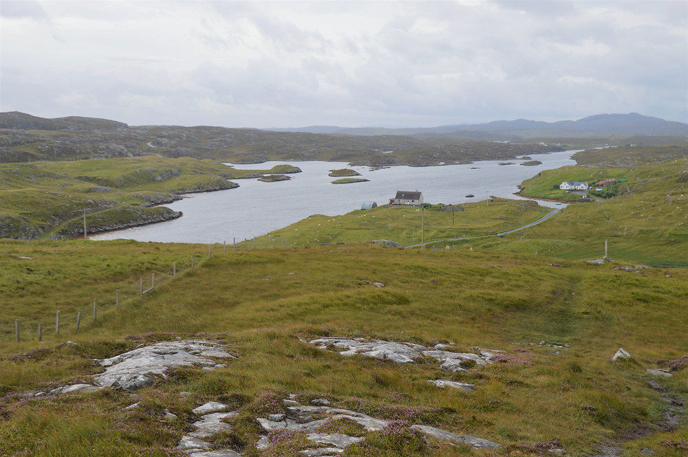 Climbing Beinn an Toib with views of Tob Bhalasaigh on Great Bernera Loop hike on the NW coast of Isle of Lewis, Outer Hebrides
