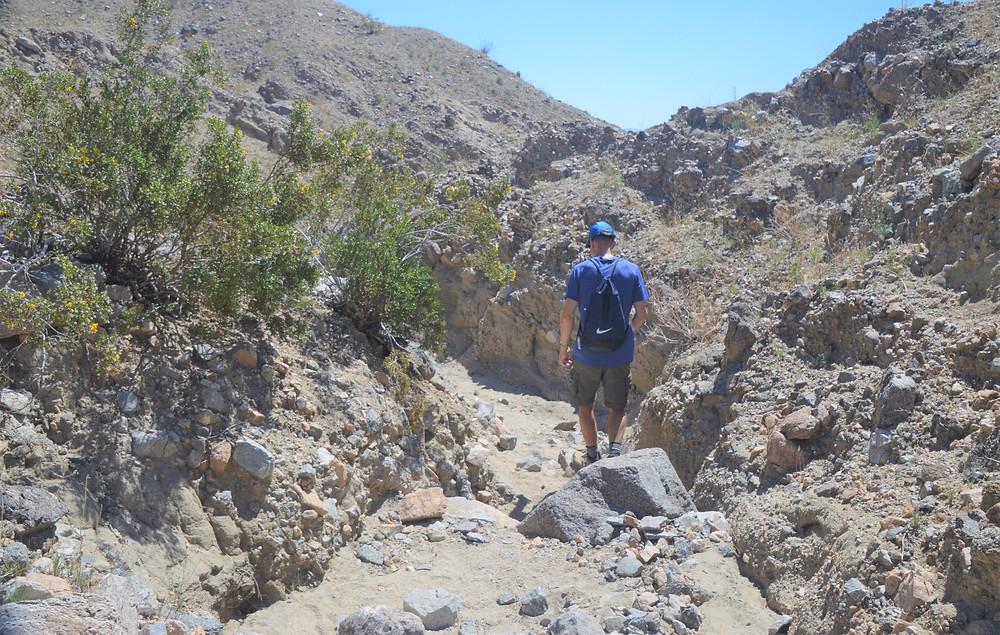 Hiking through narrow wash along Indio Hills Badland Loop Trail