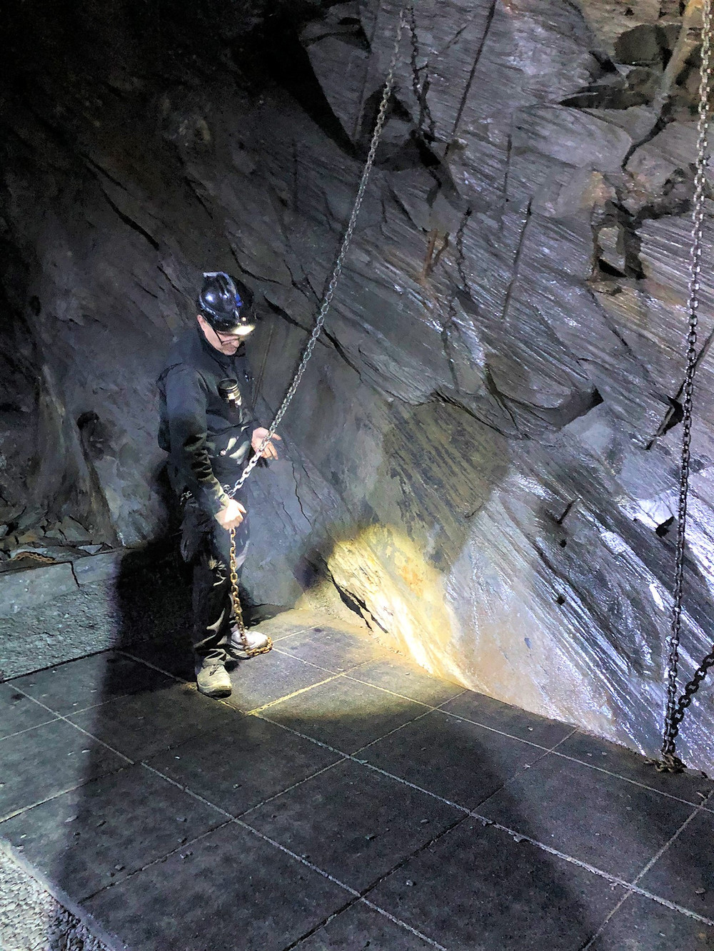 Guide demonstrating how workers used chains to secure themselves to slate chamber walls in Llechwedd Slate Quarry