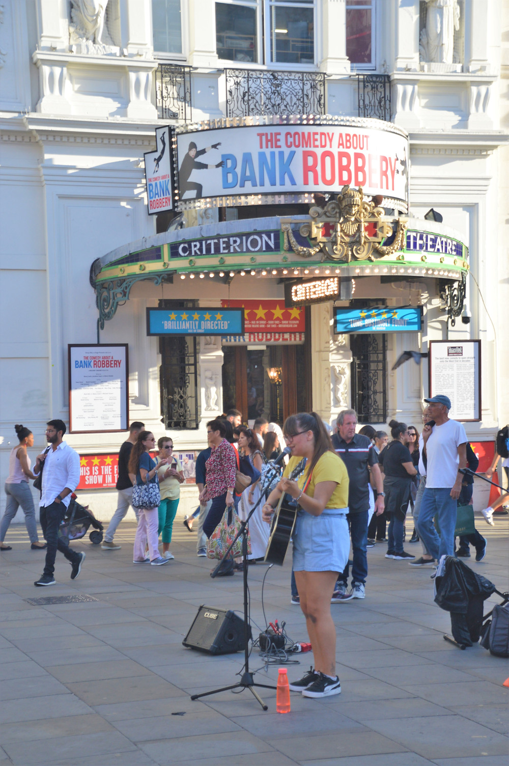 Theatre marquee for 'The Comedy About a Bank Robbery' play in London's Piccadilly Square