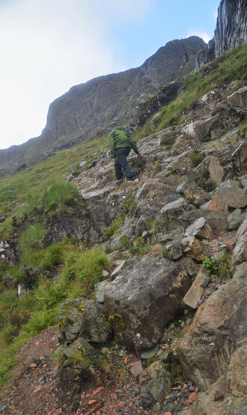 Hiking Buachaille Etive Mòr via the steep rock ledge in Coire na Tuliach path in the Scottish Highlands