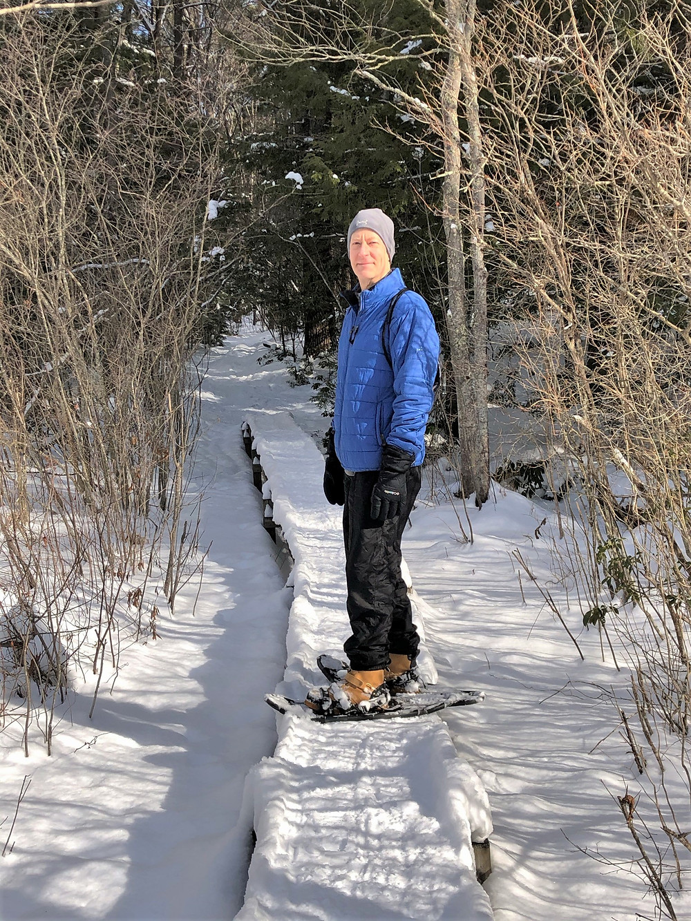 Crossing wetlands while snowshoeing at Beaver Brook Conservation Lands in Hollis New Hampshire
