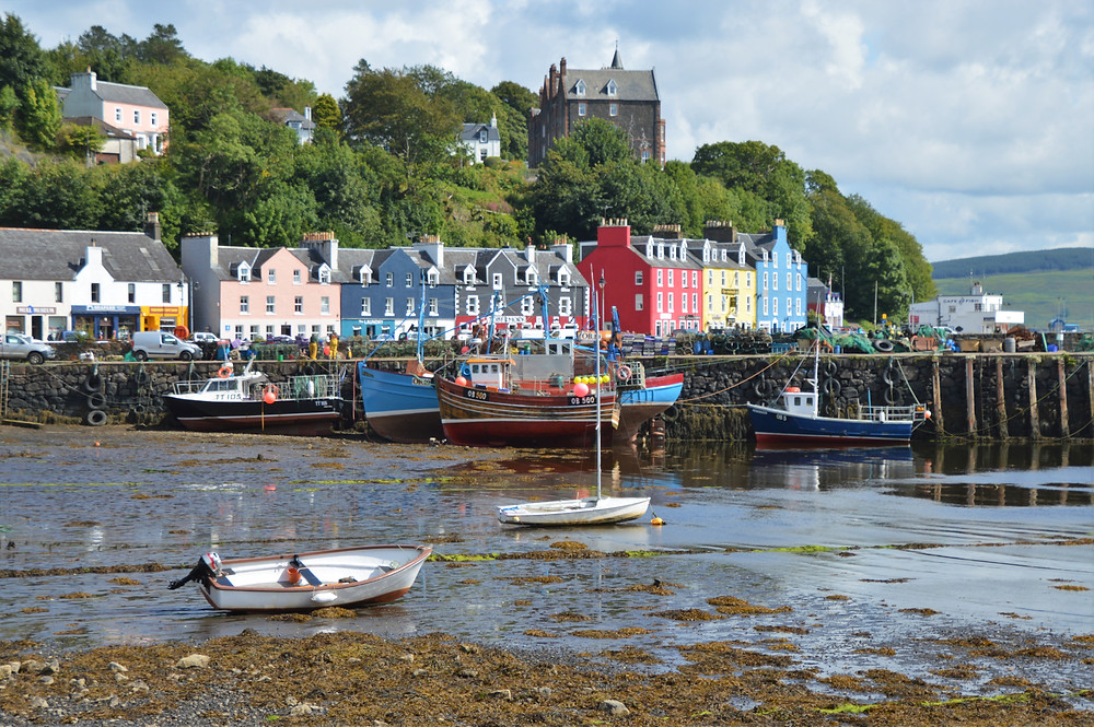 Bright colored buildings along Tobermory harbor at low tide on the Isle of Mull in Scotland
