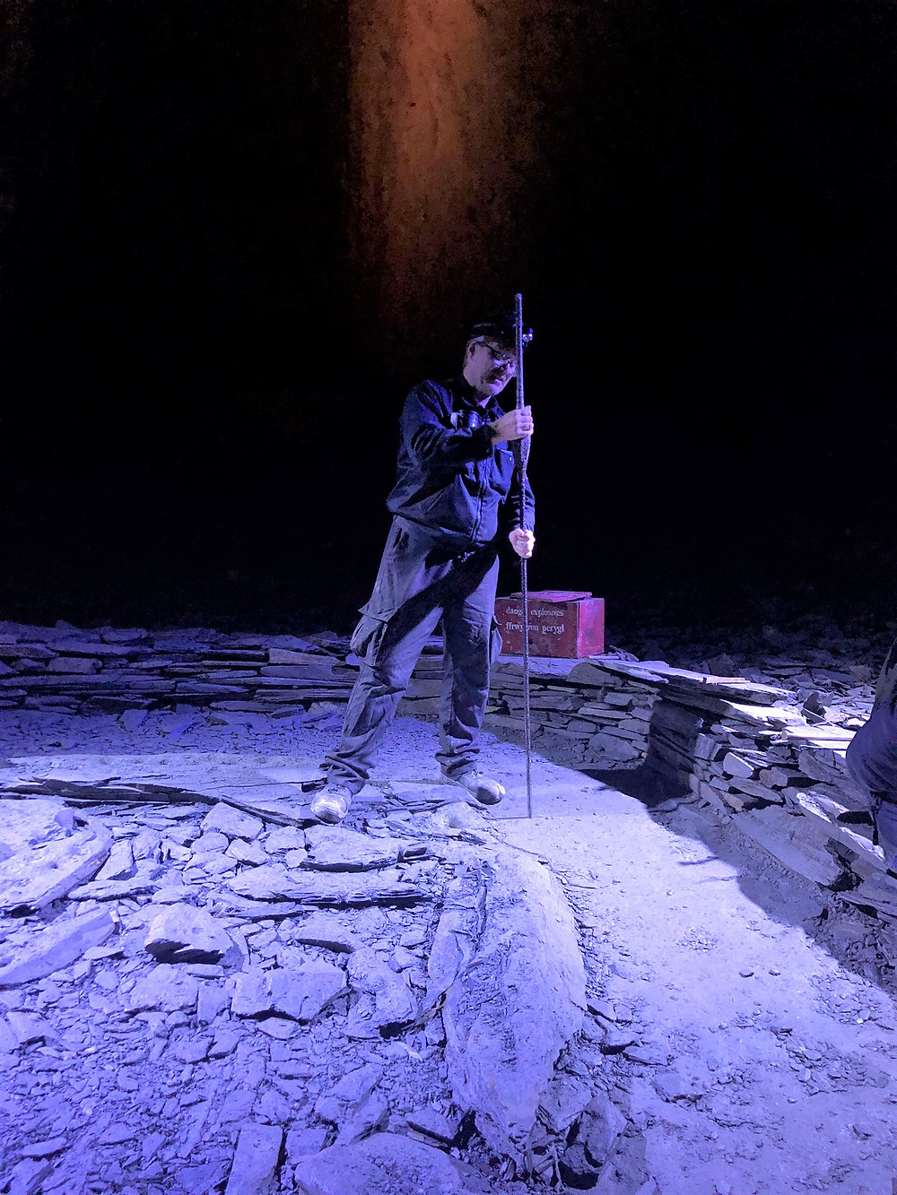 Guide demonstrating use of heavy hand tools used to make holes filled with gunpowder to open up slate chamber in Llechwedd Slate Quarry
