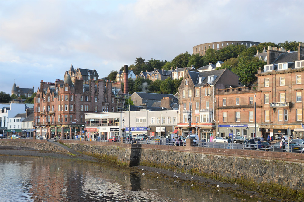 Oban harbor with McCaig's Tower in the distance. Scotland