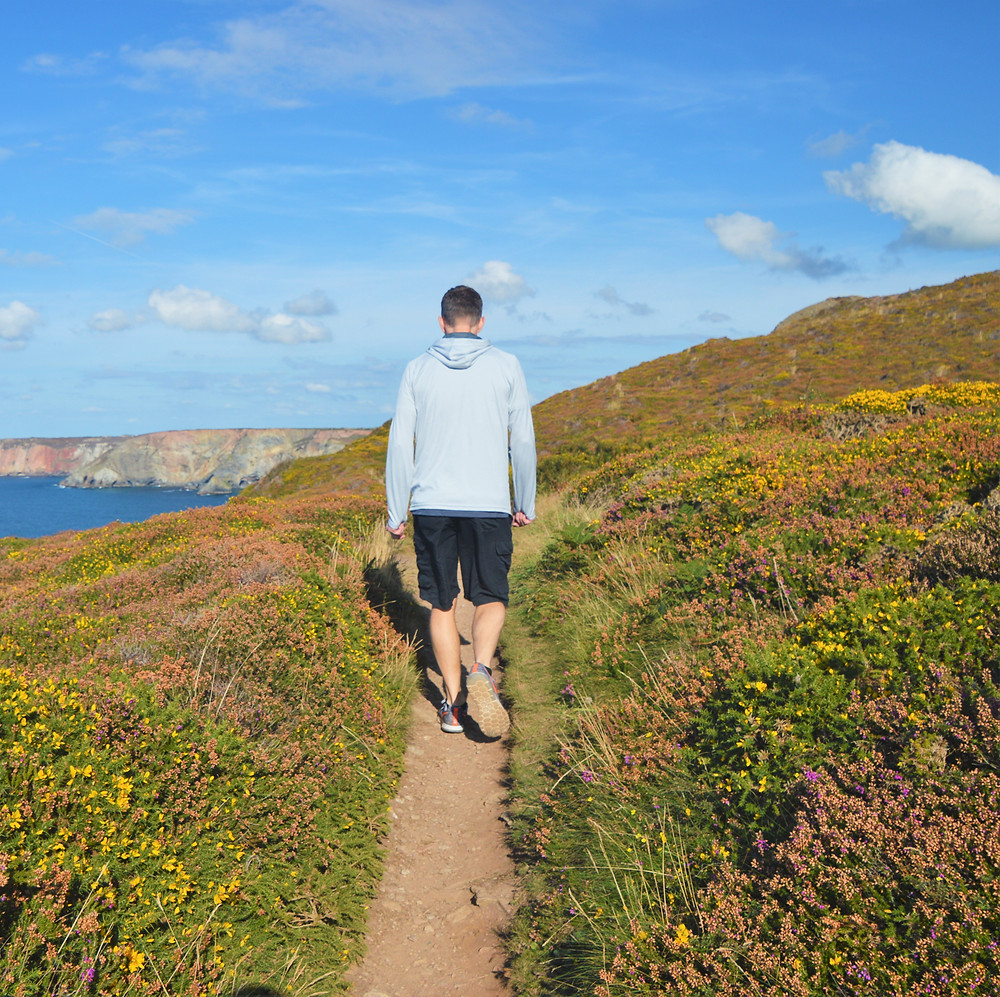 Walking the trail in St Agnes, England with views of the sea cliffs on the north coast of Cornwall
