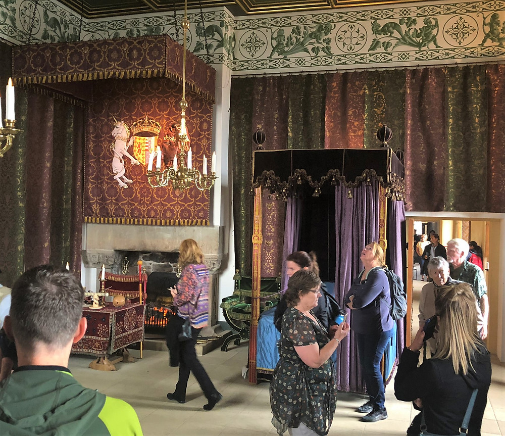 The Queen's Bedchamber in Stirling Castle with walls covered in paint, tapestry and fabrics