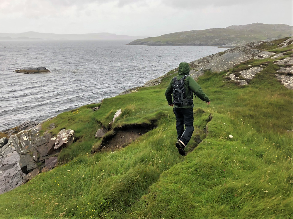 Hiking in the rain along the coastline of Loch Roag on Great Bernera Loop hike on the NW coast of Isle of Lewis, Outer Hebrides