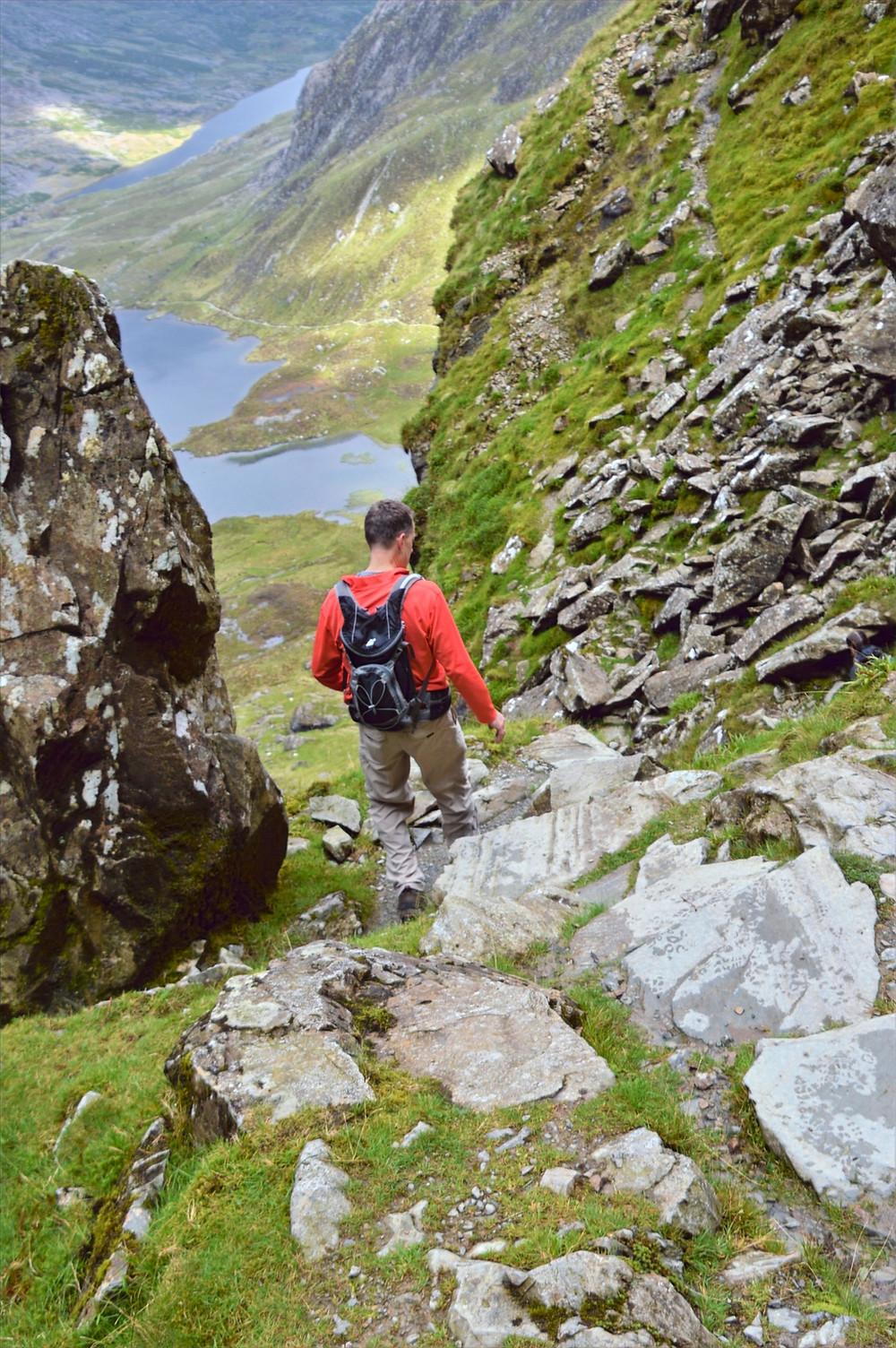 Climbing through boulder field on path from Devil's Kitchen in Snowdonia