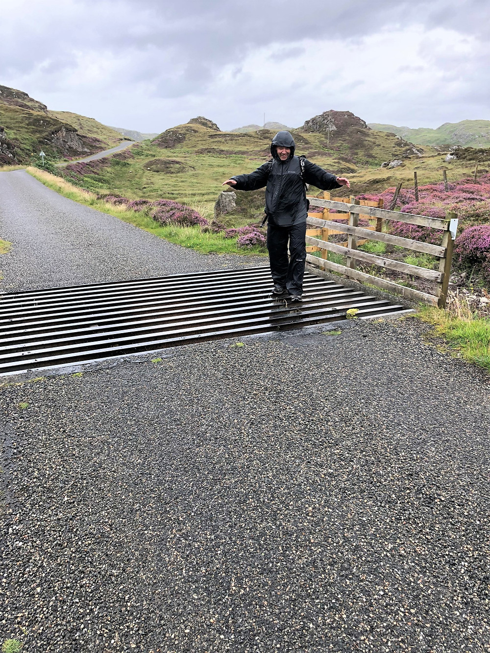 Walking in strong winds and rain the single track road to Breascleit on the Great Bernera Loop trail in the Outer Hebrides