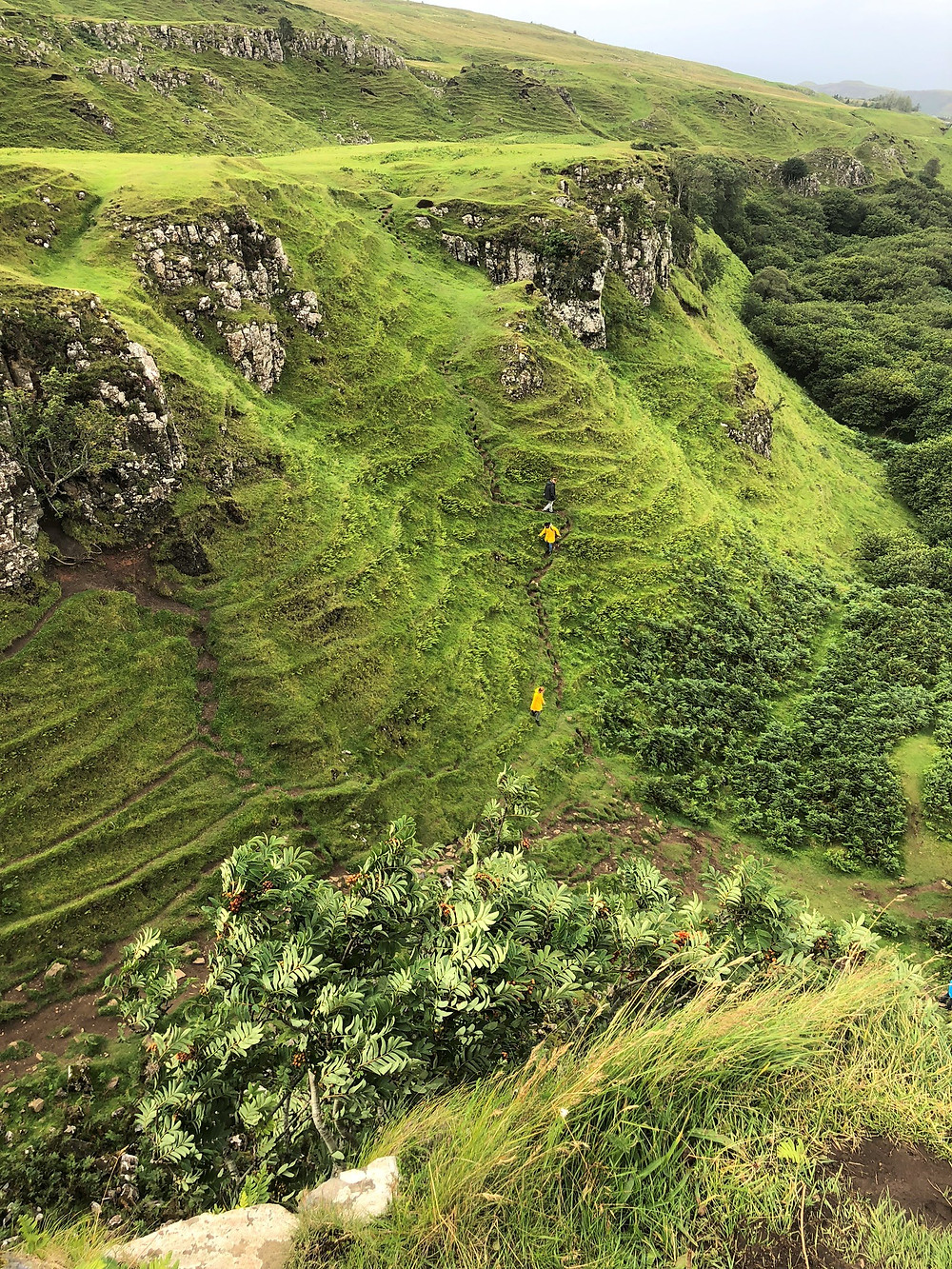 People climbing the green knolls of Fairy Glen on the Isle of Skye