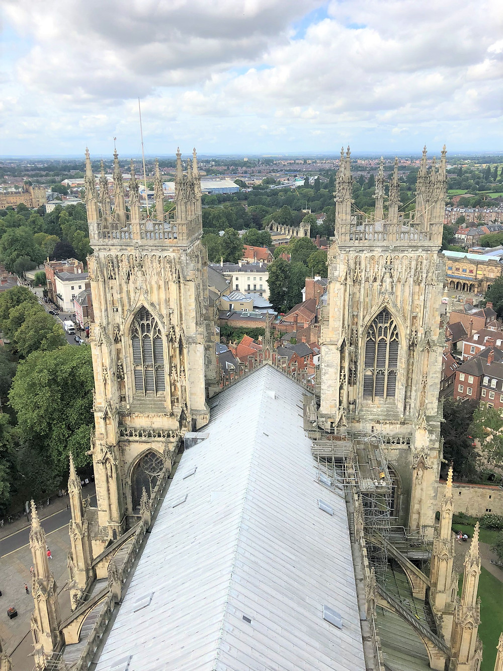 Standing on the roof of the Central Tower of York Minster with views of West Towers and surrounding village