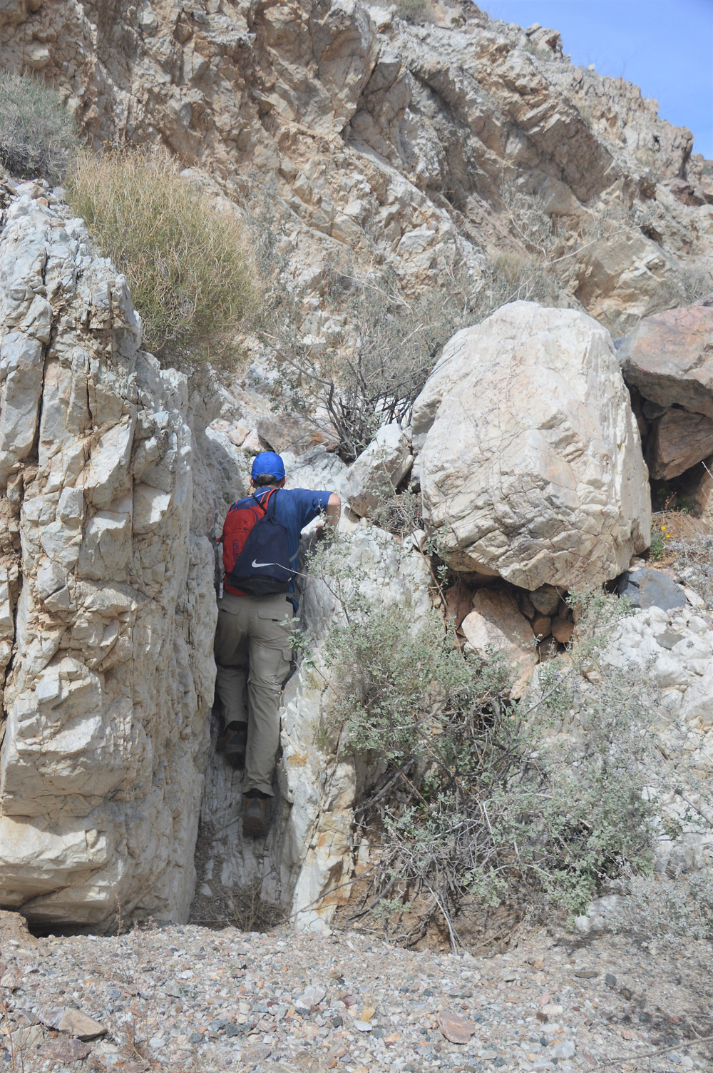 Climbing through narrow opening in rock on hike to Pinto Mountain summit in Joshua Tree National Park
