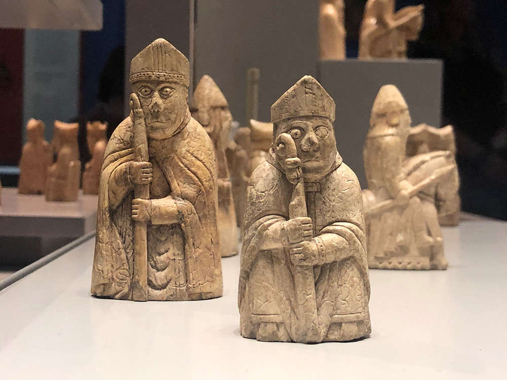 On display in the British Museum the Lewis Chessmen Bishops are wearing their mitre and holding the staff with both hands