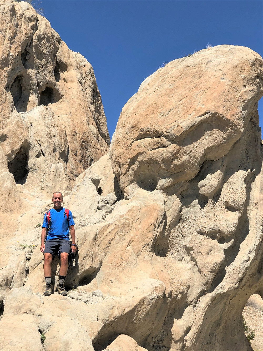 Hiker standing in wind and rain eroded sedimentary rocks along Indio Hills Badland Loop Trail