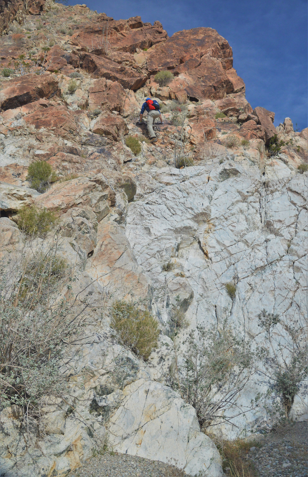 Climbing rock ledge on hike leading to summit of Pinto Mountain in Joshua Tree National Park