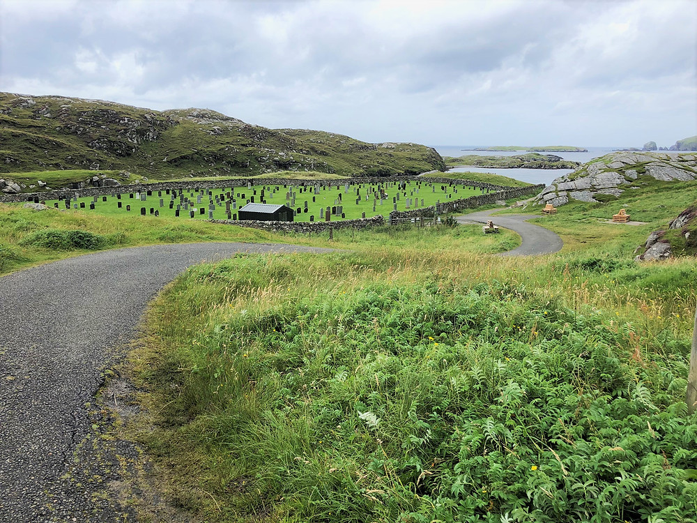 Walking the single track road pass the cemetery to Breascleit on the Great Bernera Loop trail in the Outer Hebrides